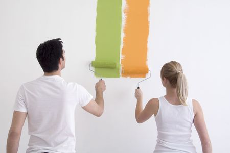 Man and Woman painting colors on a white wall.  Their backs are facing the camera.