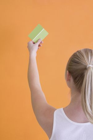 opposing views: Woman is holding up a green paint sample to orange painted wall.  Her back is facing the camera. Stock Photo