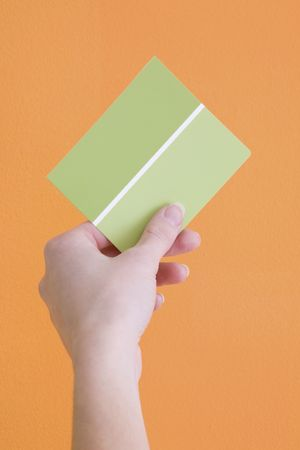 opposing views: Hand is holding up a green paint sample to an orange wall.
