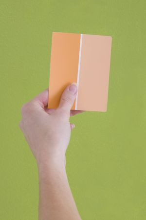 opposing views: Hand is holding up an orange paint sample to a green wall. Stock Photo