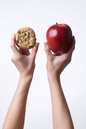 grasp: Vertical image of hands holding up a cookie and apple before a white background