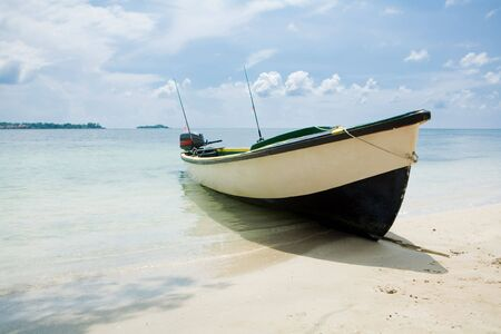 Fishing boat on a beach with water and blue skies 免版税图像