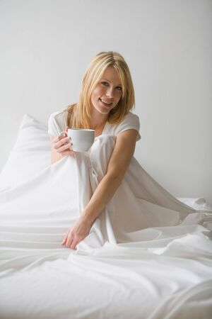 Woman sitting up in bed with white covers around her, holding a cup Stock Photo