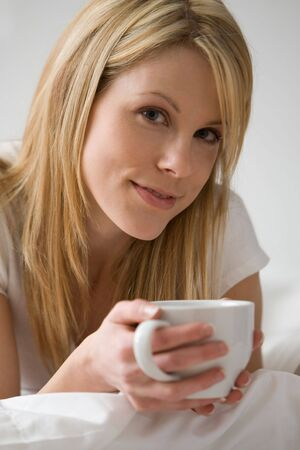 Close up of woman lying down holding a cup photo