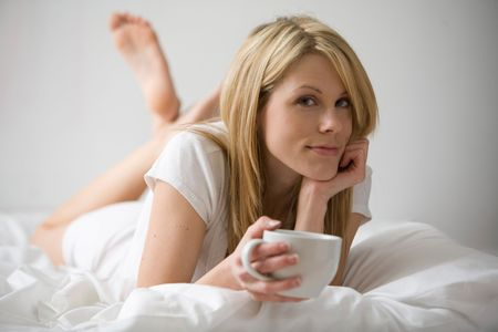 rested: Woman lying on her stomach in bed, holding a coffee cup and resting her chin on her hand Stock Photo