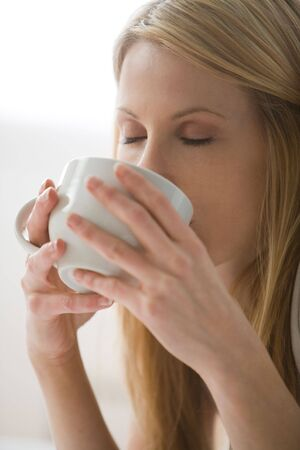Blonde woman drinking from a white cup with her eyes closed photo