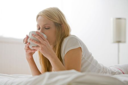 Blonde woman lying on her stomach in bed and drinking out of white cup Stock Photo