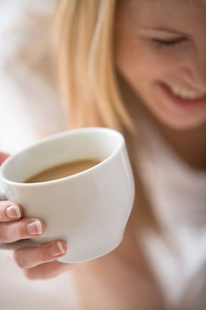 midlife: Partial face of woman holding up a white cup with coffee Stock Photo