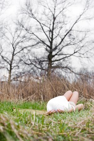 midlife: Woman lying on her back in the grass among trees Stock Photo