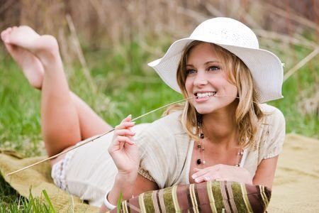 lying in grass: Mujer tumbada sobre una manta en el pasto con un largo trozo de c�sped en su boca