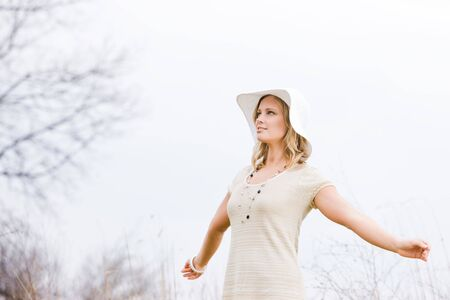 Woman in hat standing outside with her arms outstretched