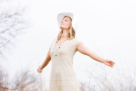 Blonde woman with hat standing outside with her face up and arms out basking in the sun