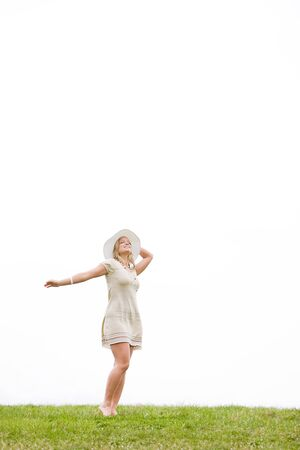 Woman with a hat and dress standing in grass with her arms outstretched 免版税图像