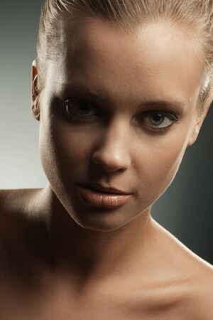 Beauty image of blonde woman with her hair up, in front of dark background