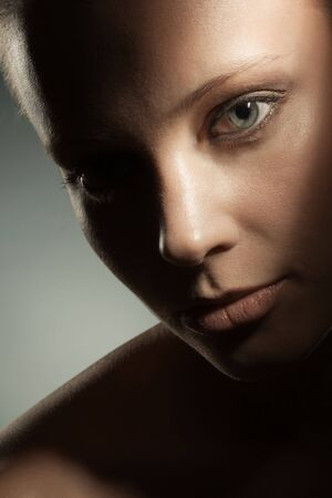 Beauty image of womans face in dark shadows