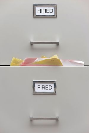 Detail of a file cabinet labeled Hired and Fired with papers overflowing from the Fired drawer.