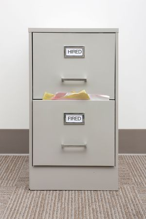 File cabinet labeled Hired and Fired with papers overflowing from the Fired drawer. 免版税图像