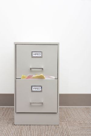 File cabinet labeled Hired and Fired with papers overflowing from the Fired drawer with copy space above. 免版税图像