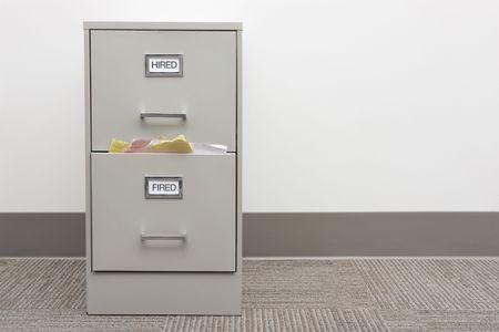 file cabinet: Archivero etiquetados contratado y despedido con papeles desbordamiento del caj�n Fired con copia espacio a la derecha.