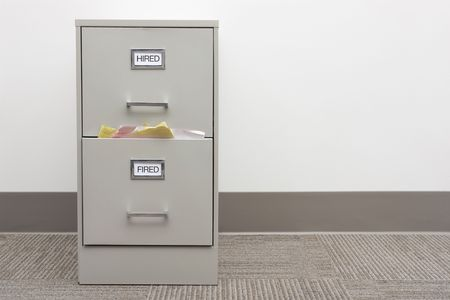 File cabinet labeled Hired and Fired with papers overflowing from the Fired drawer with copy space to right.