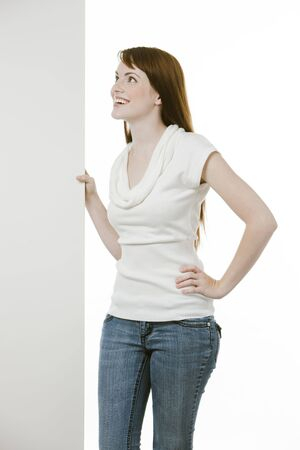 Young woman holding a blank board over white