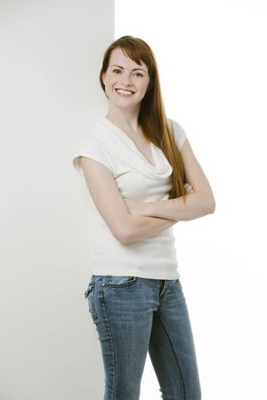 Cute young woman with hands folded smiling over white backdrop