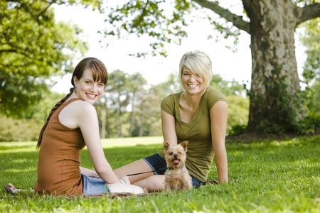 two persons only: Young women sitting with dog at a park Stock Photo