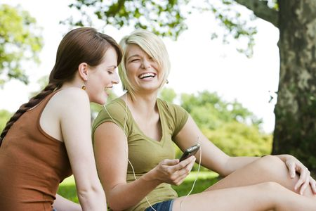 Happy young women listening to music at a park 免版税图像
