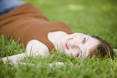 Beautiful young woman lying down of grass
