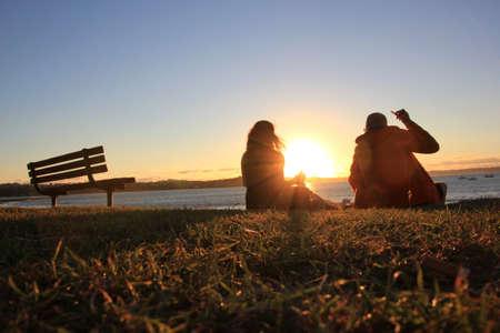 mujer mirando el horizonte: Una pareja est� viendo la puesta de sol