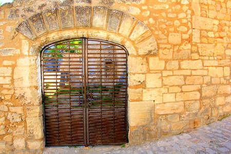 metal gate: rustic metal gate in a stone wall Stock Photo