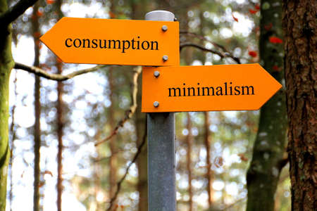 Consumption and minimalism written on a hiking sign Stock Photo