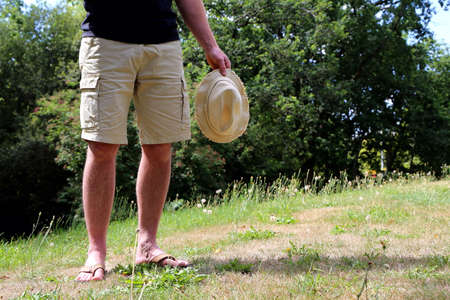 Man with shorts and has is standing in the garden