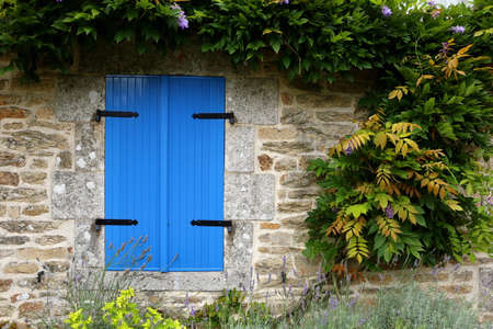 Closed blue shutters in an old stone building in rural brittany, france Zdjęcie Seryjne