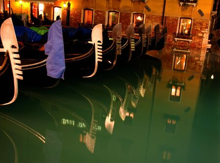reflecting: Gondolas reflecting in the water at night in Venice