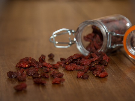 olden: Goji Berry in glass jar on olden woodwn table Stock Photo