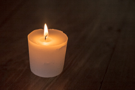 lit: portrait of white candle lit on dark wooden background