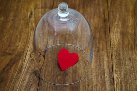 protects: Which glass case protects a small red heart on old wooden table