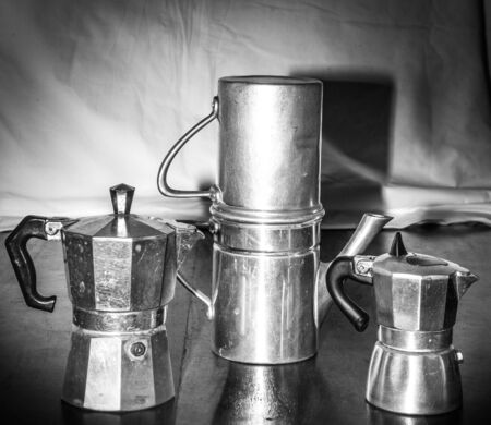 expressed: vintage set of three coffee pots on old wooden table and background tarp Stock Photo