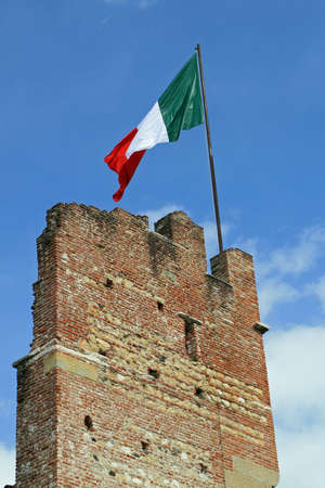 bulwark: Italian flag flying high above an ancient tower of a castle in Italy  Stock Photo