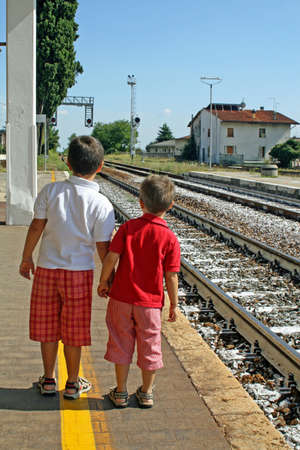 two children waiting for the train on the tracks to the station photo