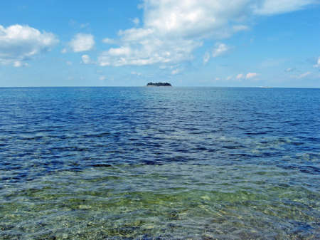 remote atoll in the middle of a blue sea in summer  photo