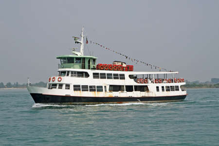 erry carries passengers and tourists to the island from the lagoon of Venice photo