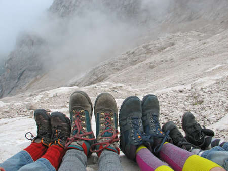 hike: hiking boots of a family rest on the Italian Alps after a walk