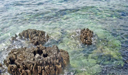 rocks in the middle of the crystal blue sea green  photo
