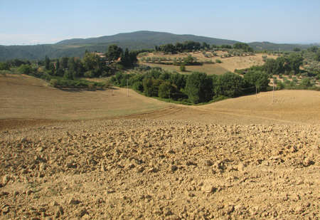 ploughing: land of ploughed fields in the hills of Tuscany in summer Stock Photo