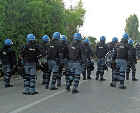 riot: uniformed police officers with shields and helmets