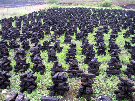 turf: veld met donkere stapels turf gebruikt om huizen te verwarmen Stockfoto
