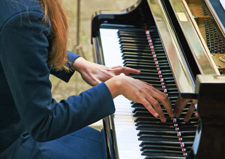hands of skilled young pianist on the piano photo