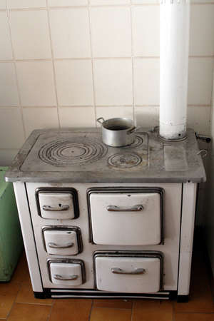 estufa: vieja estufa de leña en una vieja cocina de una casa en las montañas